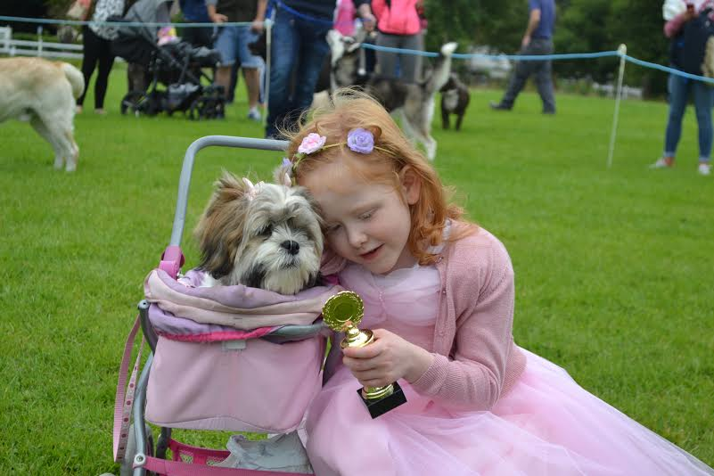 Cute as a button: A little girl enjoys Muff Festival with her pooch